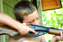 Picture of a little blond boy with a bb gun, aiming it outside from a doorway