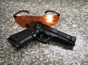 Photo of an airsoft gun and safety goggles orange in color, lying on the floor. Protection glasses are sitting behind the airsoft pistol in this picture.