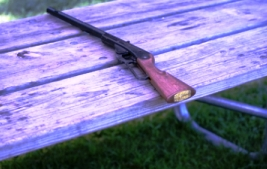 Photo of a bb gun wooden and black lying on a wood table