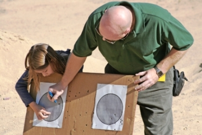 Photo of a girl father and daughter at target practice, learning how to use a gun via Airsoft safety