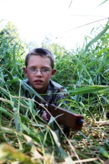 Picture of a boy in woods or small bushes representing a photo of teaching your child airsoft safety.