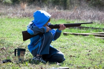 Photo of a boy in blue jacket and hood holding and aiming an airsoft rifle gun outside in the grass fields. Is airsoft dangerous? Not if you teach your children gun safety.