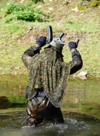 This photo represents the honor code in airsoft games, man dressed in camouflage wear with gun over his head in a surrendering manner