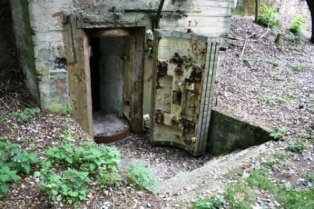 Picture of an Airsoft bunker or fort made in cement with a thick rock door swinging open