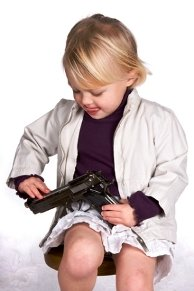Picture of a little blond boy playing with a handgun in his lap.